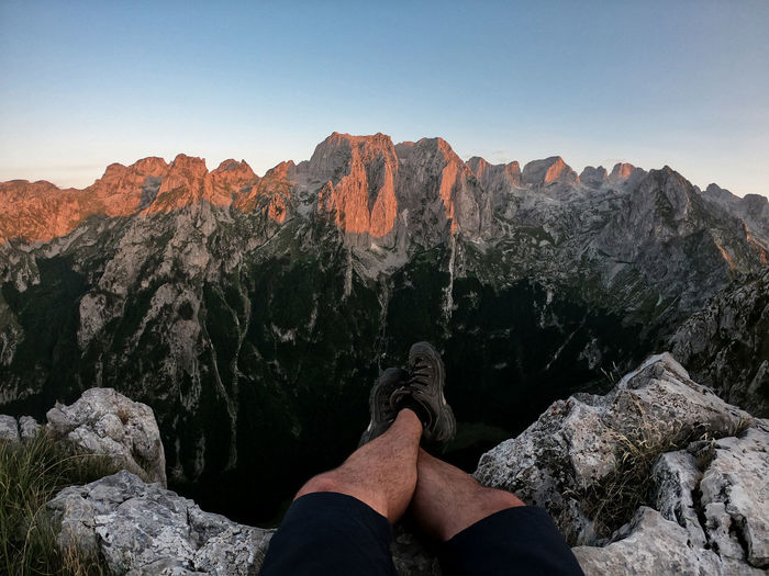 Low section of person on rock in mountains against sky