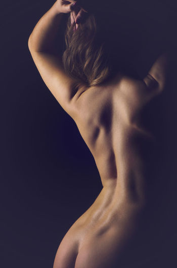 Rear View Of Naked Woman Against Black Background
