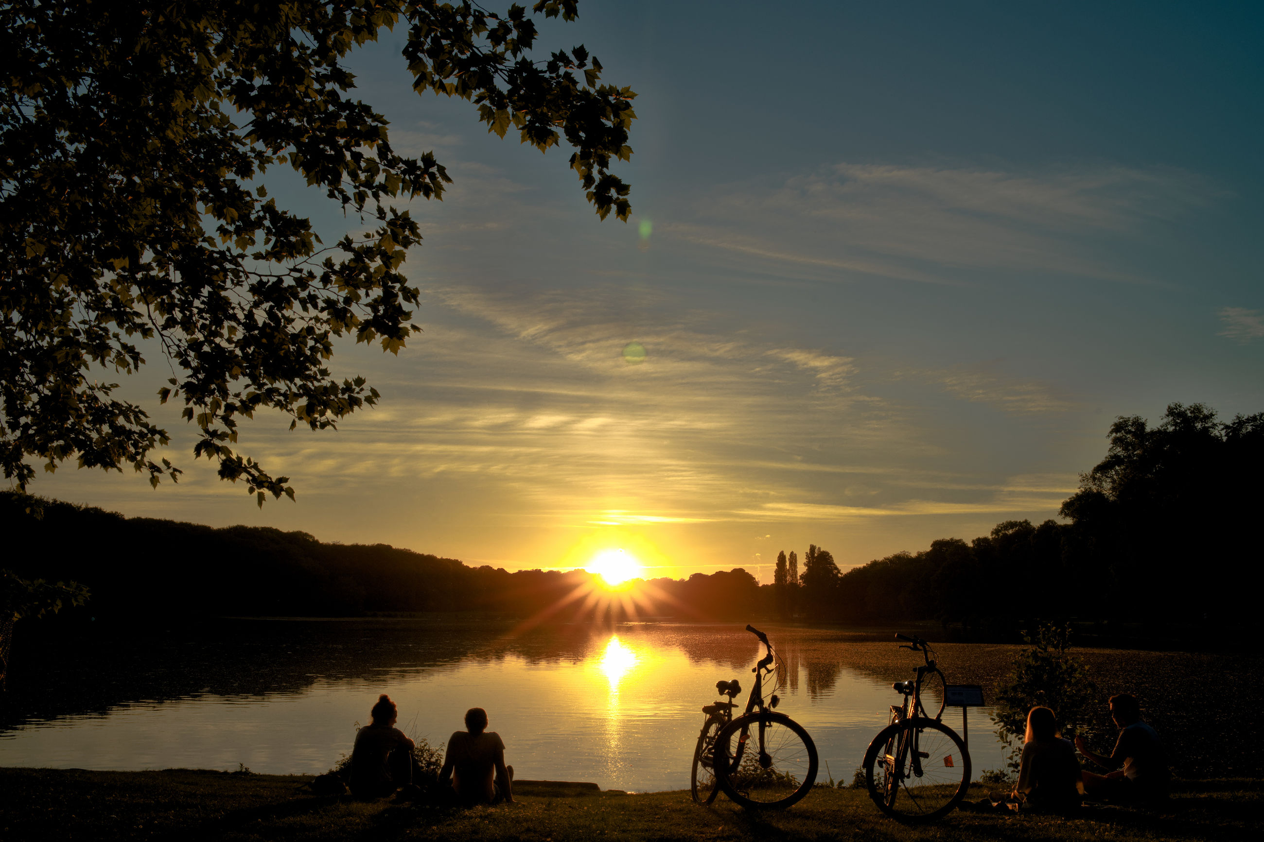 sunset, sky, silhouette, water, beauty in nature, tree, orange color, real people, group of people, scenics - nature, men, plant, cloud - sky, nature, leisure activity, bicycle, tranquility, lifestyles, sun, outdoors