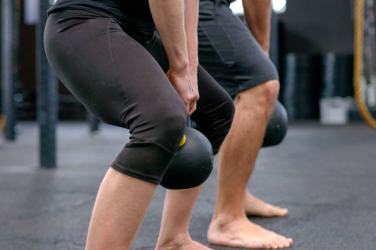 Low Section Of Athletes Exercising With Kettlebell In Gym