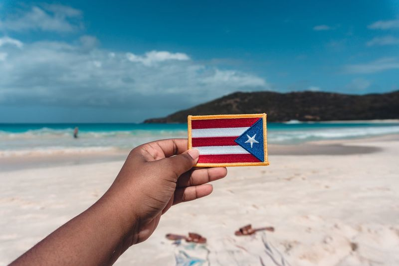 Cropped hand holding flag at beach against cloudy sky