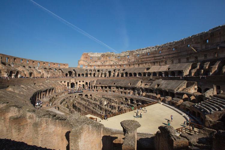 Historic coliseum against blue sky