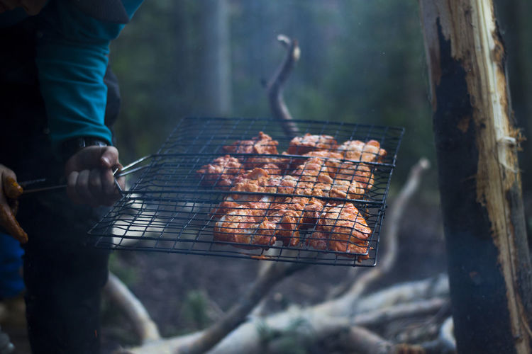 Midsection of man holding meat in metal grate at campsite