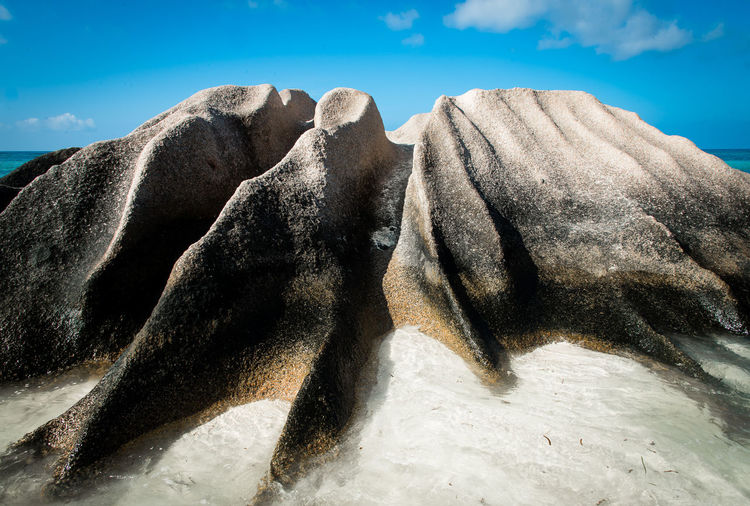 Rock Formation On Beach Against Sky