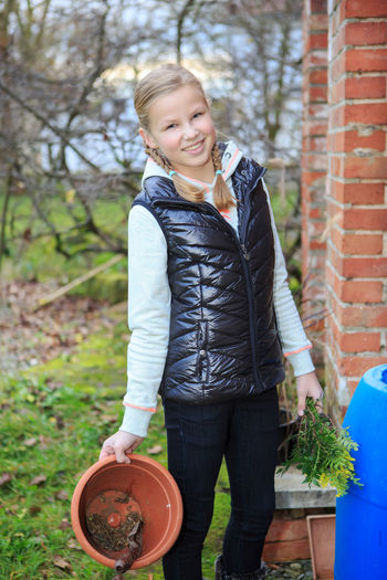 Portrait of smiling young woman holding flower pot and leaves