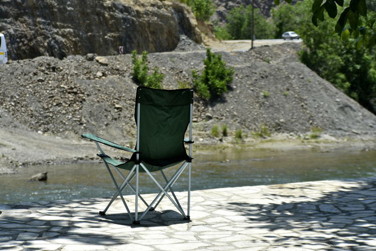 Chair on rock by lake