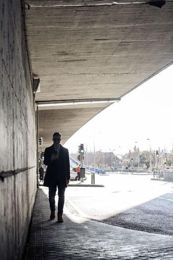 Rear view of man walking on bridge