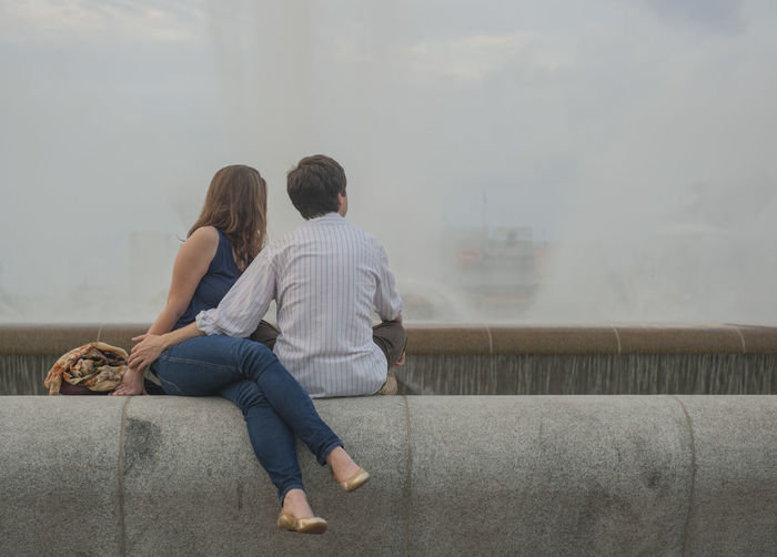 Young couple sitting on retaining wall of fountain
