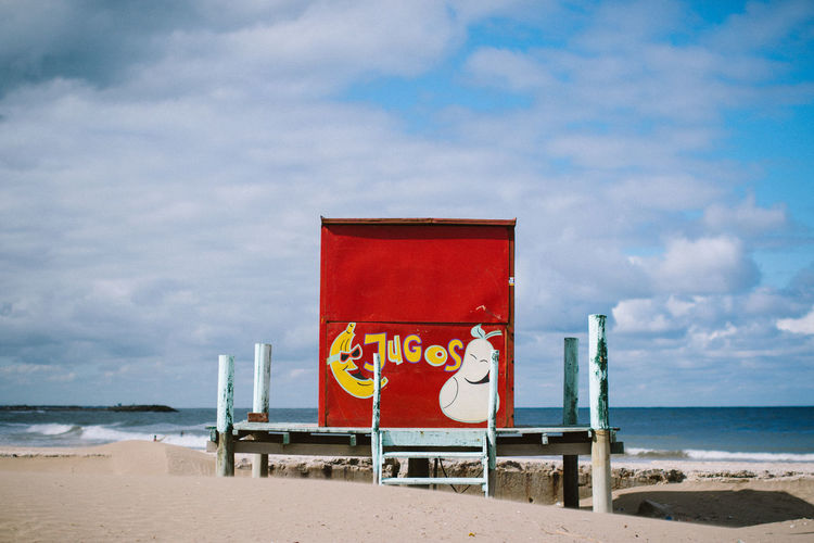 Red lifeguard hut on beach against cloudy sky