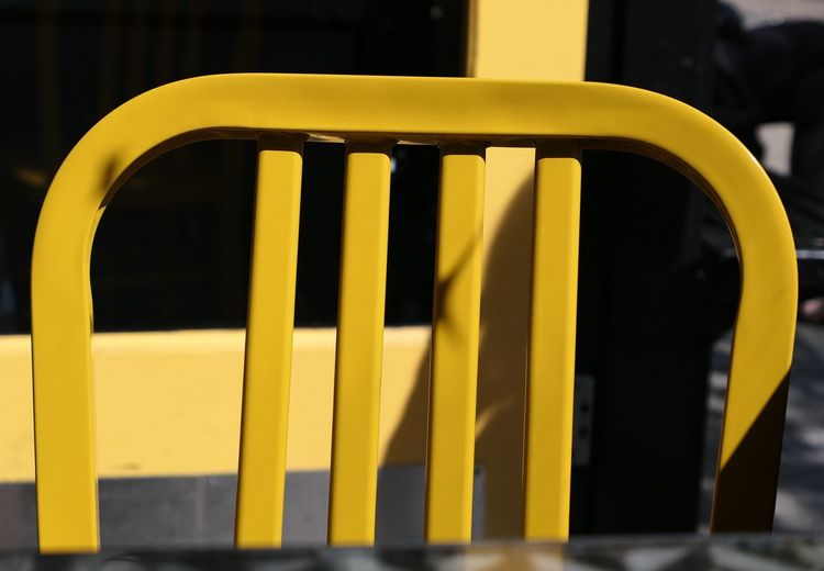 Close-up of yellow chair at outdoor cafe