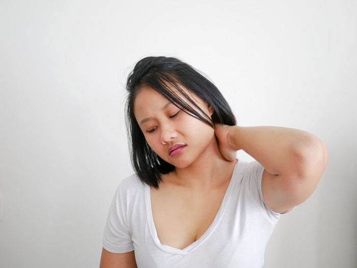 Tired Young Woman Suffering From Neckache Against White Wall