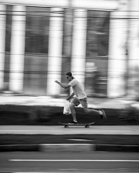 Blurred Motion Of Man Skateboarding On Road
