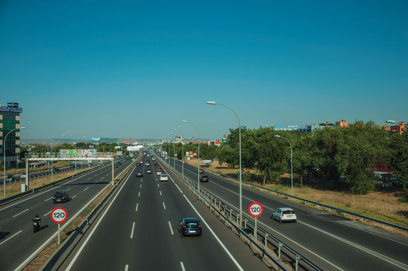 Cars on highway in city against clear sky