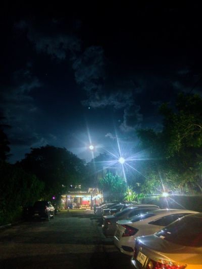 Cars on illuminated street against sky at night