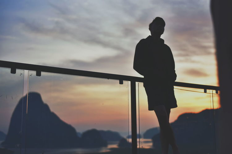 Low angle view of silhouette man standing at railing against sky