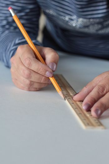 Midsection Of Man Drawing Line On White Table Using Ruler And Pencil