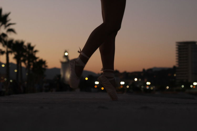 Low section of teenage girl ballet dancing on footpath in city
