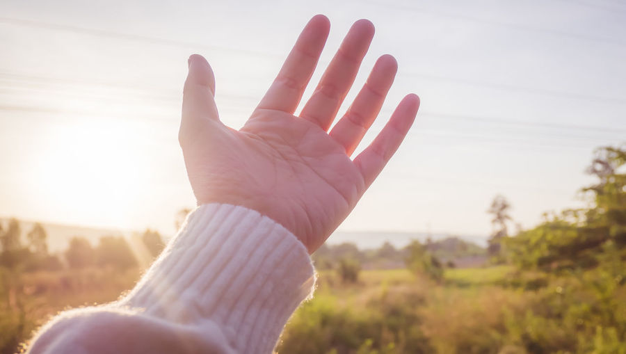 Close-up of hand against sky