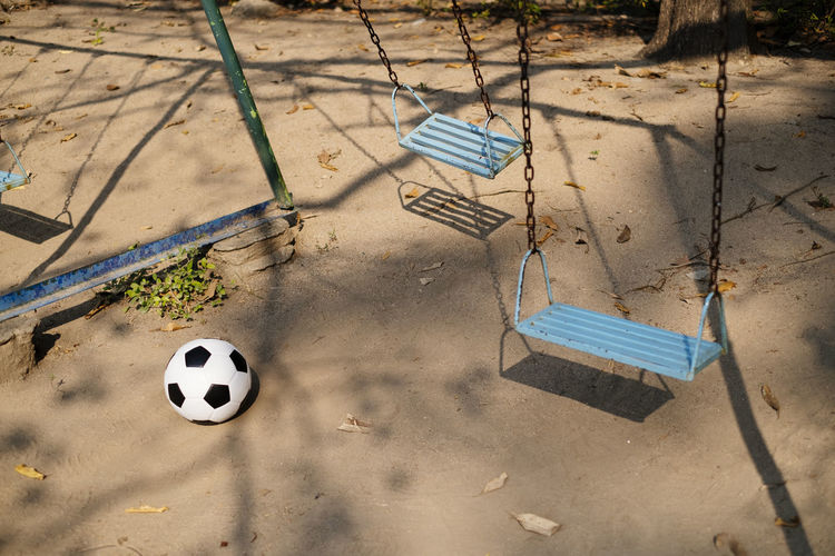 Soccer ball and swings in playground