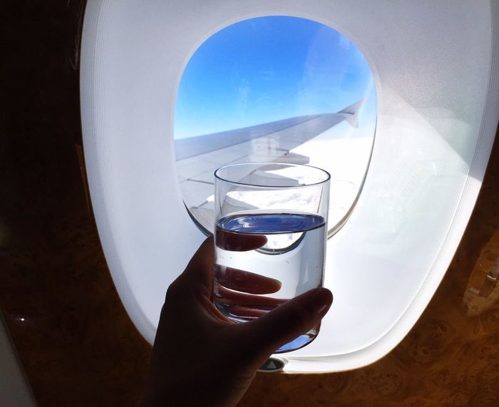 Staying hydrated during flight when traveling Traveling Flying In Business Class Business Class Window Seat Airplane Shot Airplane Wing Airplane Glass Of Water Hydrate Yourself Staying Hydrated Hydration Flying Human Hand Real People One Person Human Body Part Holding Personal Perspective Drink Lifestyles