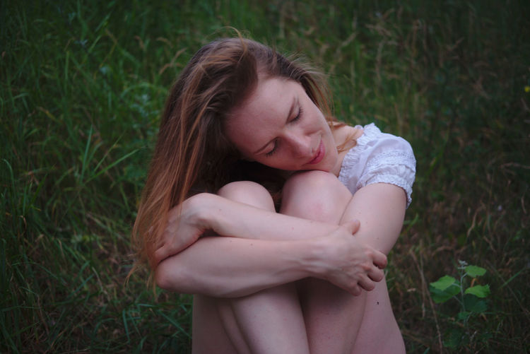 Woman With Eyes Closed Hugging Knees While Sitting On Grassy Field