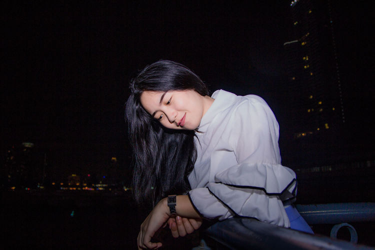 Smiling young woman looking down while standing in city at night
