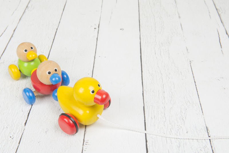 Wooden duck pull kids toy with a string on a white wooden background Toy Wood - Material Table High Angle View Indoors  Multi Colored Duck Pull Toy Copy Space Wooden Toys Wood