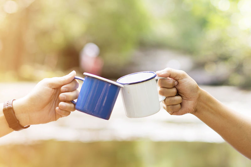 Clink glasses a cup of coffee together in the wild, blur background Body Part Coffee Coffee - Drink Coffee Cup Cup Day Drink Finger Focus On Foreground Food And Drink Hand Holding Human Body Part Human Hand Human Limb Lifestyles Mug Outdoors People Real People Refreshment Two People