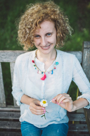 Portrait Of Smiling Woman Holding Flower While Sitting On Bench