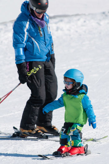 Little Boy And His Ski-Trainer On Ski Lesson Winter Sport Skiing Learning Toddler  Ski Instructor Winter Sport Ski Lessons Trainer Blue White Snow Little Boy Teaching Happiness Enjoyment Smiling Explaining  Ski Trainer Education Outdoors Nature Protection Downhill Skiing Leisure Activity