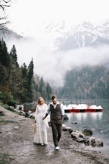 Two happy people in love the bride and groom in wedding outfits embrace by the lake and mountains