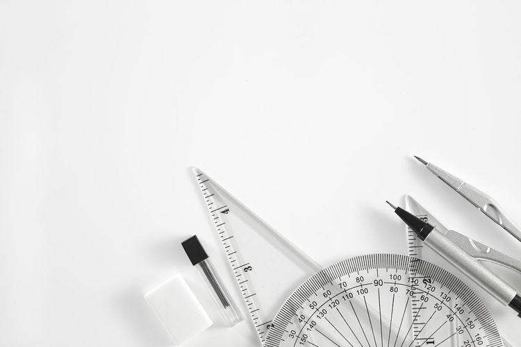 Close-up of set square with protractor on white background