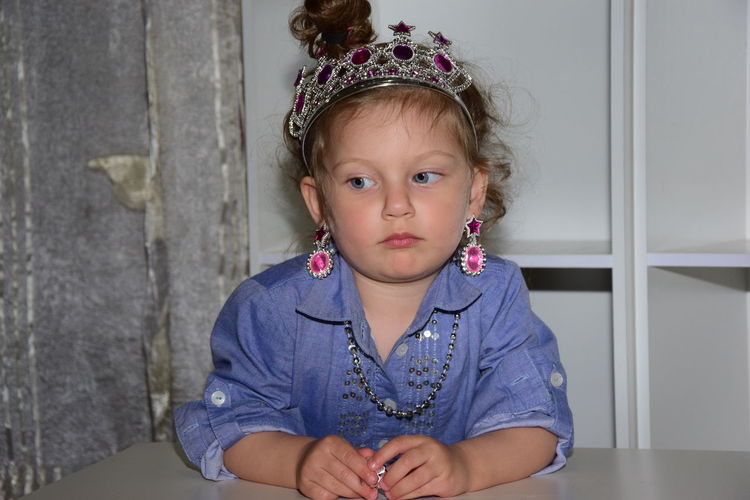 Cute girl wearing crown at table