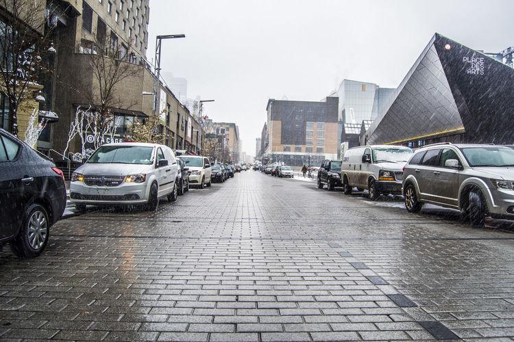 Cars on wet street in city against sky