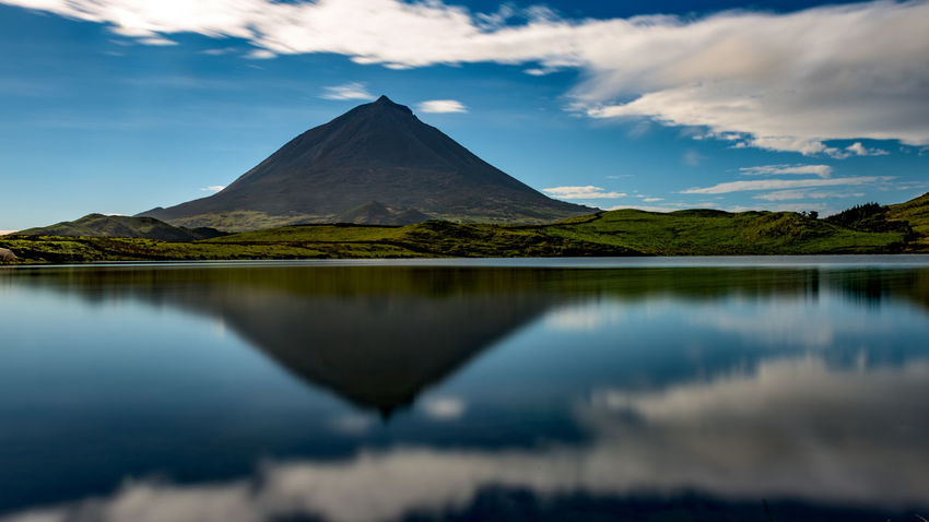 "It took me a day or two to find the best location to get a mirror image of mount Pico in the clear. But here she is. Mount Pico is the highest mountain in Portugal and lies on the island bearing her name, in the mid atlantic Azores. It's a very imposing stratovolcano and the first thing we saw after the plane opened it's doors. (Nikon D810 ƒ/14.0 24mm 20"" iso 31 + Lee Big Stopper) 16x9 Azores Copy Space Ilha Do Pico Long Exposure Mirror Mountain No People Panorama Learn And Shoot: Balancing Elements Picoftheday Portogallo Reflection Symmetry Volcano Water Reflections Www.benjaminvanderspek.com EyeEm Best Shots - Landscape EyeEm Nature Lover EyeEm Best Shots Landscapes With WhiteWall The Great Outdoors - 2016 EyeEm Awards The Great Outdoors With Adobe"