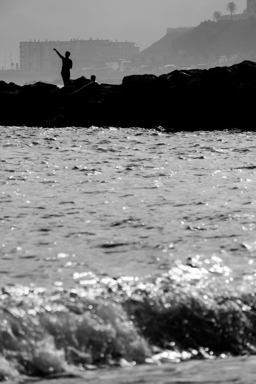 SILHOUETTE PERSON ON SHORE AGAINST SKY