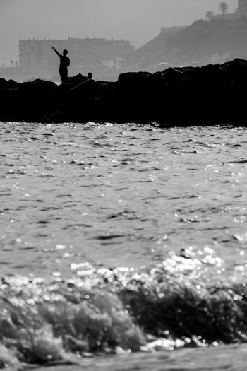 Silhouette person on beach against sky