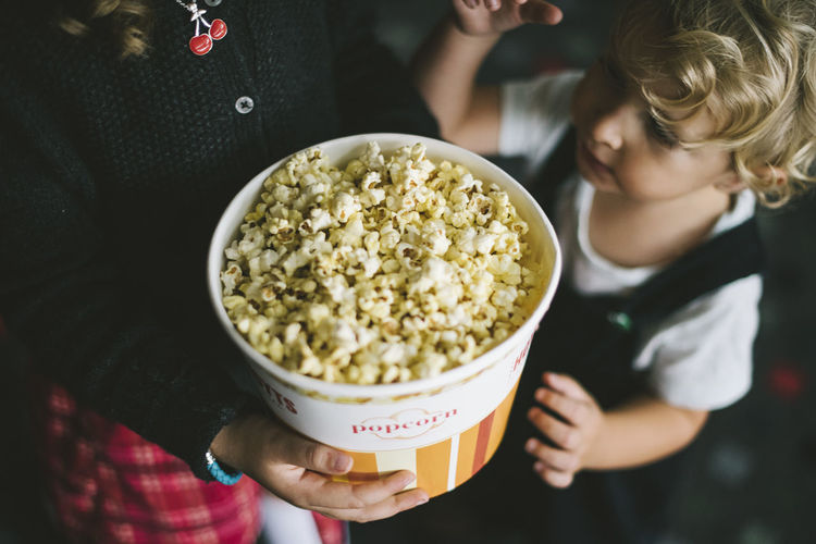 High angle view of siblings eating popcorn