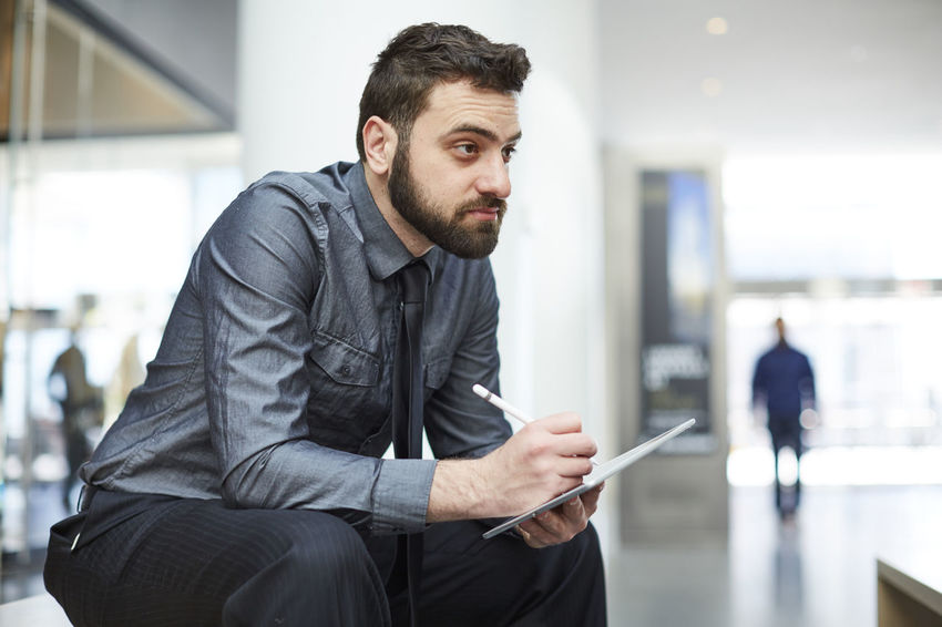 Young bearded Brazilian man works on an iPad in New York City Beard Brazilian Businessman Corporate Business Finance Inside Ipad Light Man Mobile One Man Only Only Men Sitting Tablet Technology Tie Web Design Well-dressed Working