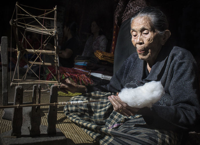 Woman making thread from cotton while sitting on floor