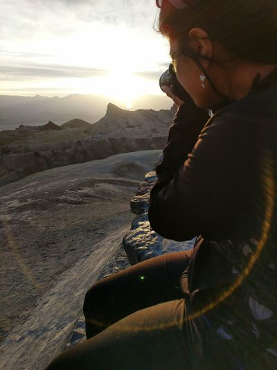 Side View Of Young Woman Photographing While Sitting On Mountain At Death Valley National Park