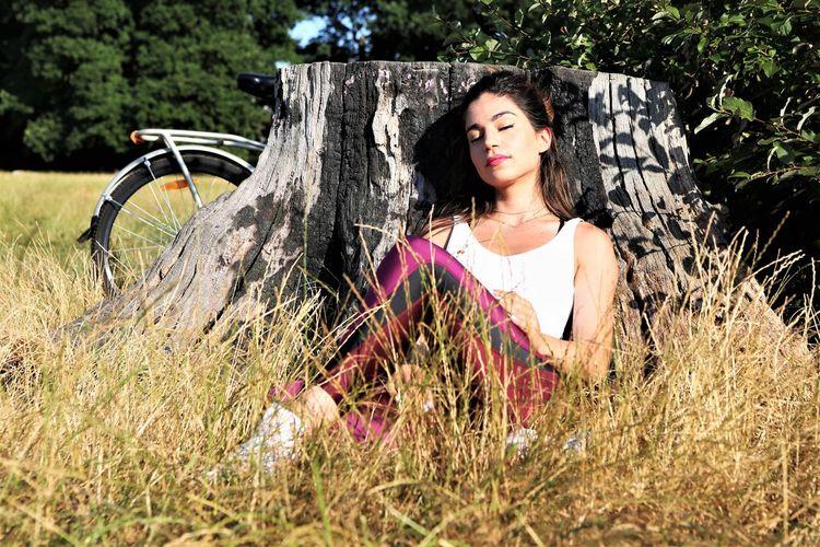 Woman resting against tree stump on grassy field