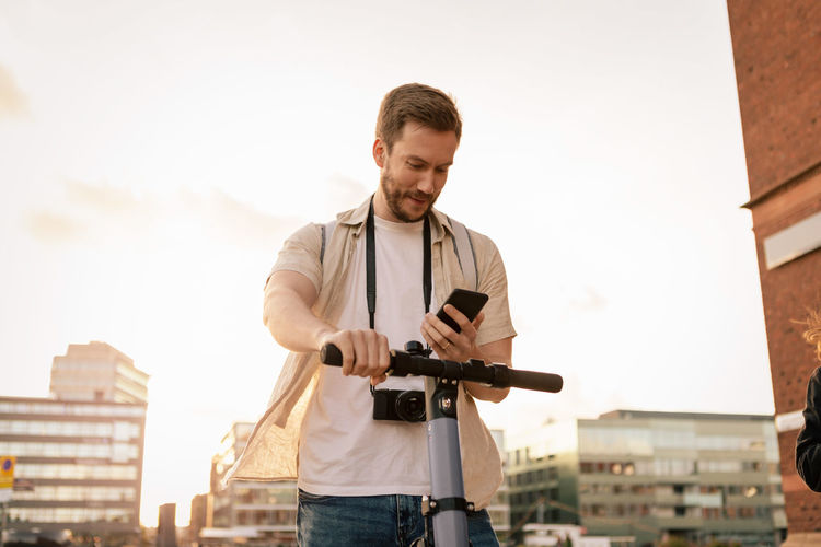 Young man photographing with city in background