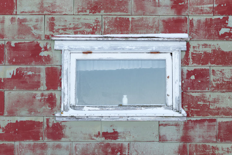 Small white vase behind small white window in an small, old cabin with red paint peeling off Red Deterioration Bad Condition Barn Wood - Material Peeling Off Weathered Paint Vase Full Frame In The Center Remote Built Structure Window Architecture Brick Building Exterior Brick Wall Wall - Building Feature Wall Day No People White Color Old Glass - Material Building Outdoors Reflection Design Shape Abandoned Window Frame