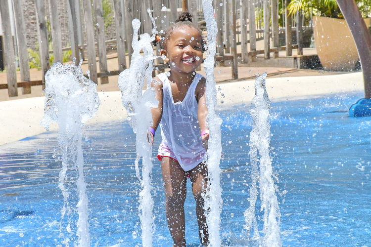 Happy girl playing with fountain at water park