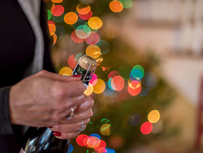 Midsection of woman opening champagne bottle during christmas