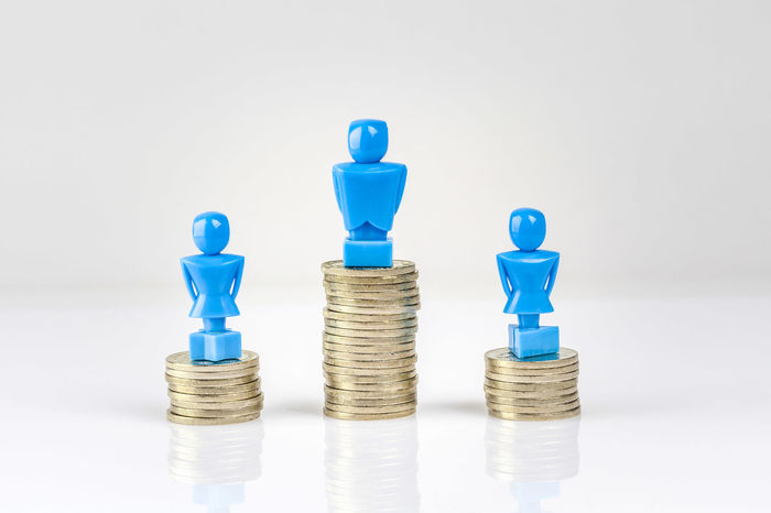 One male and two female figurines standing on piles of coins. Income inequality concept. Arrangement Bar Graph Blue Business Business Finance And Industry Close-up Coins Day Female Figurines  Gender Equality Indoors  Large Group Of Objects Male No People Pile Of Coins Stack Still Life Studio Shot Wage Gap White Background