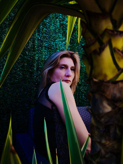 Woman looking away by plants