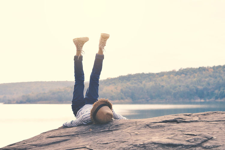 Person with feet up lying on rock against clear sky