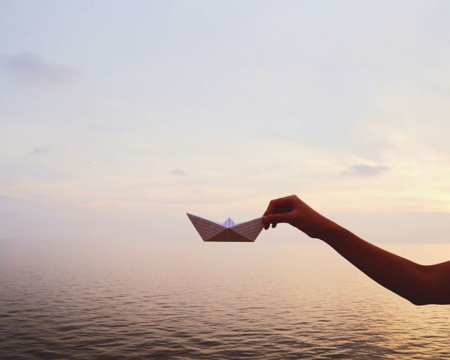 Cropped image of hand holding paper boat over sea against sky